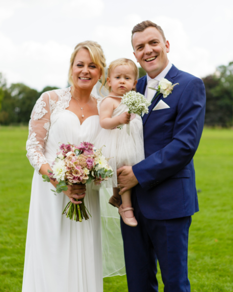 Hannah, her husband & Lily at their wedding